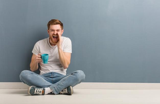 Młody rudzielec studencki mężczyzna siedzi na podłoga krzyczy coś szczęśliwego z przodu. on trzyma kubek kawy.