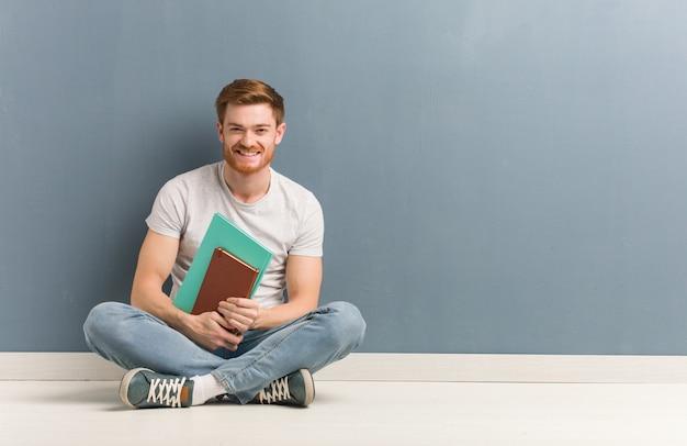 Młody rudzielec studencki mężczyzna siedzi na podłoga rozochoconej z dużym uśmiechem