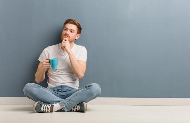 Młody rudzielec studencki mężczyzna siedzi na podłoga wątpić i wprawiać w zakłopotanie. on trzyma kubek kawy.