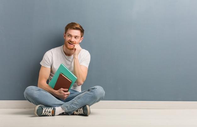 Młody rudzielec studencki mężczyzna siedzi na podłoga zrelaksowany myśleć o czymś patrzeje pustą przestrzeń.