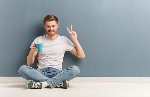 Młody rudzielec studencki mężczyzna siedzi na podłogowej zabawie i szczęśliwy robi gescie zwycięstwo. on trzyma kubek kawy.