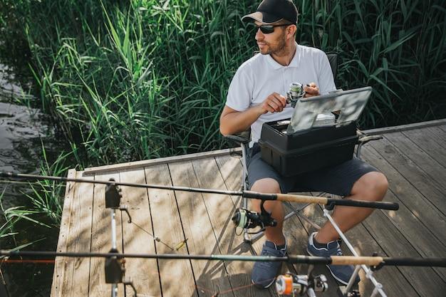 Młody rybak łowiący na jeziorze lub rzece. zajęty poważny facet siedzi w składanym krześle i trzyma rolkę. przygotowanie do wędkowania. dwie wędki obok niego do łowienia ryb. sam na zewnątrz.
