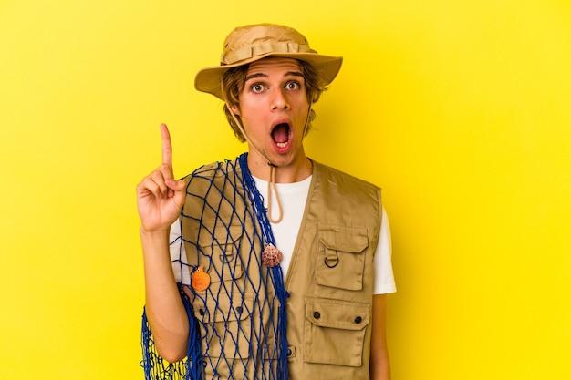 Młody rybak z makijażem trzymający siatkę na białym tle na żółtym tle mający pomysł, koncepcję inspiracji.