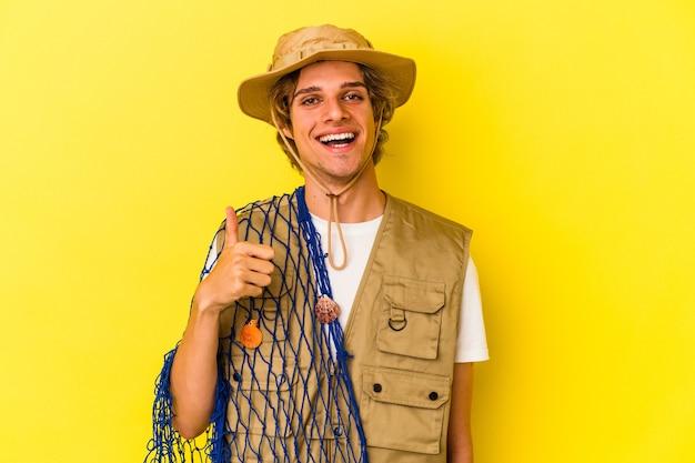 Młody rybak z makijażem trzymający siatkę odizolowaną na żółtym tle uśmiechający się i unoszący kciuk w górę