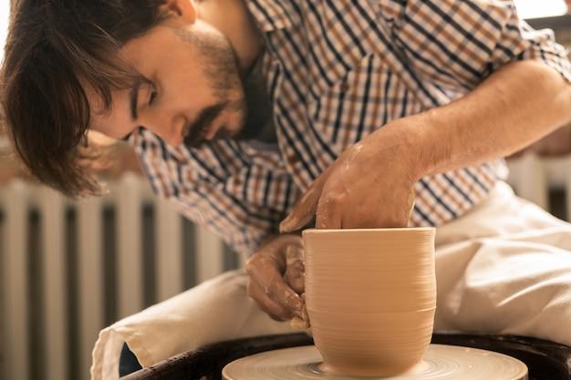 Młody rzemieślnik pracujący nad nowym glinianym przedmiotem podczas kształtowania go podczas obracania się na kole garncarskim