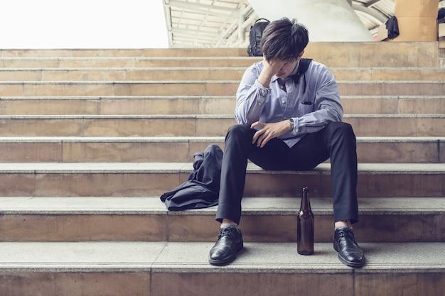 Młody salaryman siedzi stres i przygnębiony butelką alkoholu z powodu bezrobocia
