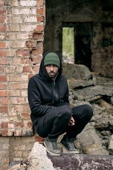Młody samotny mężczyzna w zwykłym ubraniu siedzi w ruinach