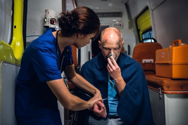 Młody sanitariusz rozmawiający z rannym mężczyzną, próbujący go uspokoić