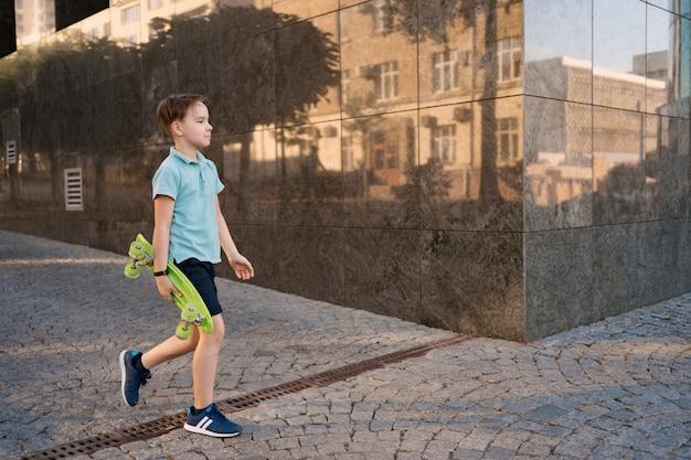 Młody school fajny chłopiec w jasnym ubraniu, chodzący z penny board w rękach