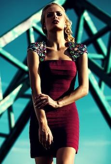 Młody seksowny blond kobieta model w wieczór czerwieni sukni pozuje na niebieskiego nieba tle