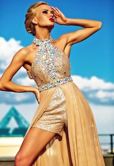 Młody seksowny blond kobieta model w wieczór koloru żółtego sukni pozuje na niebieskiego nieba tle