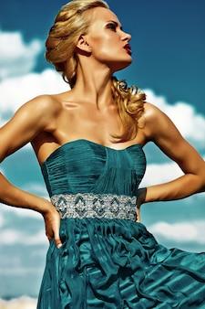 Młody seksowny blond kobieta model w wieczór sukni pozuje na niebieskiego nieba tle