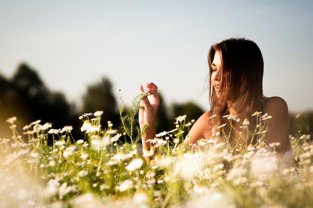 Młody seksowny brunetki kobiety lying on the beach na trawie i ono uśmiecha się na letnim dniu z zieloną naturą i rzeką