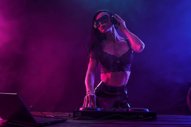Młody seksowny dj z okularami przeciwsłonecznymi odtwarzający muzykę