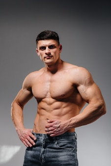 Młody seksowny sportowiec z doskonałymi abs pozuje w studio topless w dżinsach na tle. zdrowy styl życia, prawidłowe odżywianie, programy treningowe i odżywianie na odchudzanie.