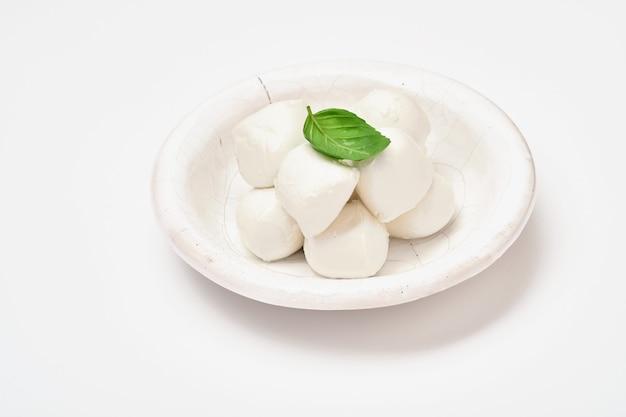 Młody ser mozzarella z liściem bazylii w białym talerzu ceramicznym na białym tle