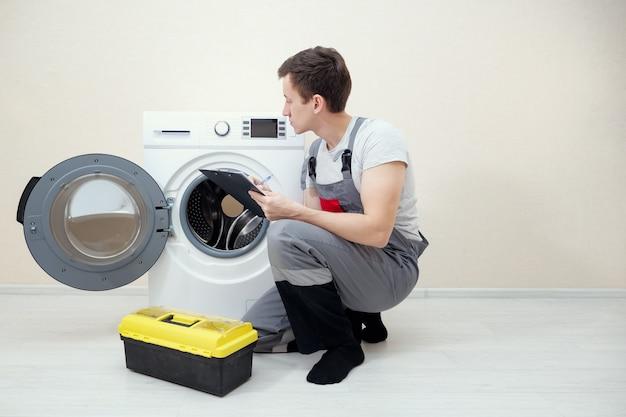 Młody serwisant sprawdza zbliżenie uszkodzonej pralki