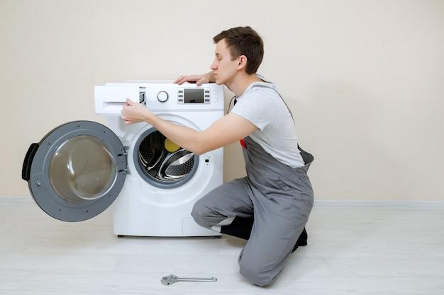 Młody serwisant w szarym mundurze naprawia zepsutą pralkę, copyspace