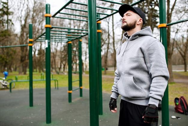 Młody siłacz przygotowuje się do treningu na boisku latem w mieście