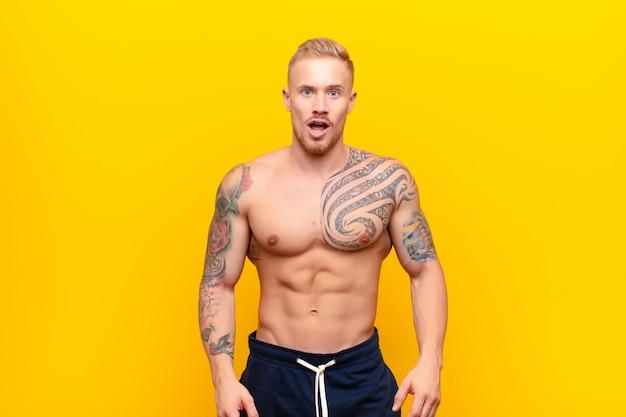 Młody silny blondyn wyglądający na zszokowanego, wściekłego, zirytowanego lub rozczarowanego, z otwartymi ustami i wściekłością na żółtej ścianie