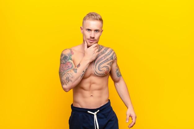 Młody silny blondyn wyglądający poważnie, zdezorientowany, niepewny i zamyślony, wątpiący w opcje lub wybory na żółtej ścianie