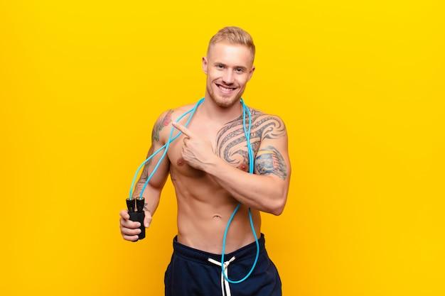 Młody silny blondynka mężczyzna uśmiecha się wesoło, czuje się szczęśliwy i wskazując na bok i do góry, pokazując obiekt w przestrzeni kopii z skakanka