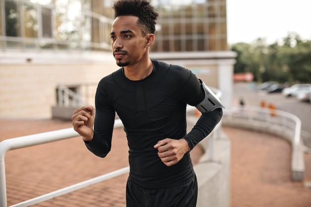 Młody, silny brodaty mężczyzna o ciemnej karnacji w czarnym t-shircie z długimi rękawami i szortach biega na zewnątrz i ćwiczy w dobrym nastroju
