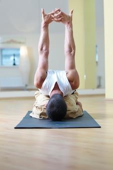 Młody silny mężczyzna robi ćwiczenia jogi. adho mukha virasana w studio jogi
