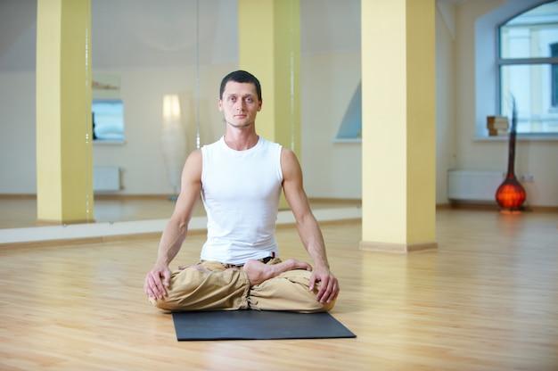 Młody silny mężczyzna robi ćwiczenia jogi. lotos pozuje i medytuje nogami padmasana w studio jogi