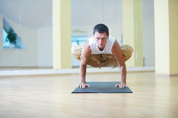 Młody silny mężczyzna robi ćwiczenia jogi. padma bakasana lotos żuraw pozuje w studio jogi