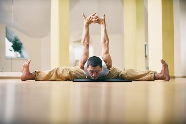 Młody silny mężczyzna robi ćwiczenia jogi - samakonasana prosty kąt stanowią w studio jogi