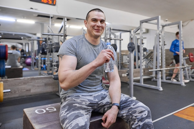 Młody silny mięśniowy mężczyzna w gym wody pitnej od butelki.