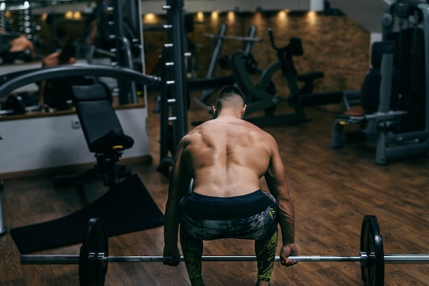 Młody, silny, muskularny mężczyzna bez koszuli podnoszący sztangę z odwróconymi plecami