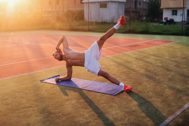 Młody silny oddany mężczyzna robi brzuszki na boisku treningowym. poranny trening wczesnym latem.