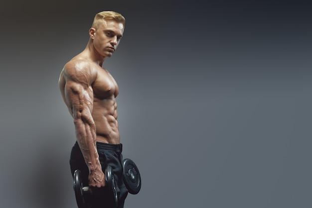 Młody silny sprawny muskularny spocony mężczyzna z dużymi mięśniami trening krzyżowy trening z hantlami w sali gimnastycznej. skopiuj wolne miejsce po prawej stronie