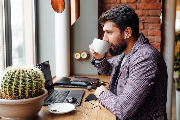 Młody skoncentrowany brodaty biznesmen w słuchawkach, używający laptopa i pijący kawę latte
