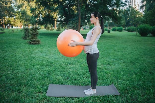 Młody skoncentrowany kobieta w ciąży stanąć na kolega z jogi w parku i trzymać piłkę fitness pomarańczowy. ona ćwiczy