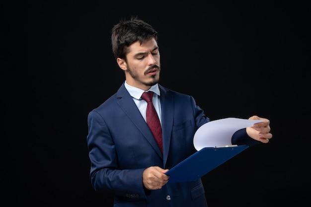 Młody skoncentrowany męski pracownik biurowy w garniturze trzymający dokumenty i sprawdzający zawarte w nim informacje na izolowanej ciemnej ścianie