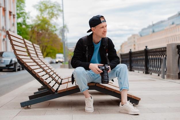 Młody, skoncentrowany, milenijny fotograf płci męskiej, próbuje zrobić zdjęcie na profesjonalnym aparacie w plenerze