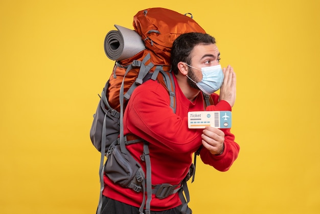 Młody skoncentrowany podróżnik w masce medycznej z plecakiem trzymającym bilet wzywający kogoś na żółto