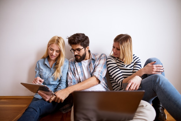 Młody skoncentrowany stylowy biznes siedzący na podłodze opierał się o ścianę, patrząc na tablet i laptop.