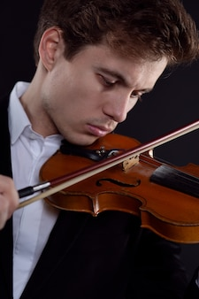 Młody skrzypek gra na starożytnym instrumencie na ciemnym tle