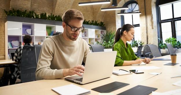 Młody skupiony kaukaski mężczyzna noszący okulary pracuje na laptopie, siedząc przy biurku ze swoim