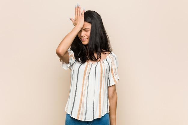 Młody śliczny chiński nastolatek zapomina coś, bije czoło dłonią i zamyka oczy.