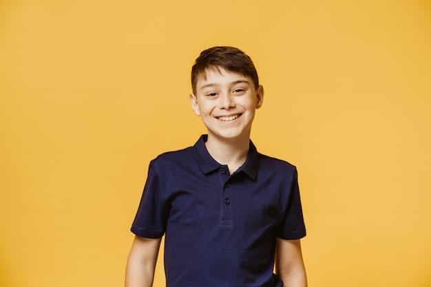 Młody śliczny kaukaski chłopiec, szeroki lśniący uśmiech, nosi ciemnofioletową koszulkę, patrząc na aparat nad żółtą ścianą. modele na ścianie. koncepcja pozytywnych ludzi.