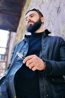 Młody śliczny młody facet z elektronicznym papierosem