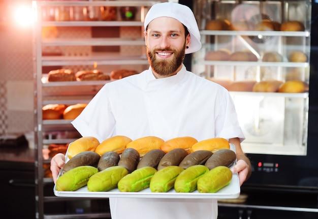Młody śliczny piekarz w białym mundurze trzyma tacę z kolorowymi rolkami dla hot dog na powierzchni piekarni lub fabryki chleba