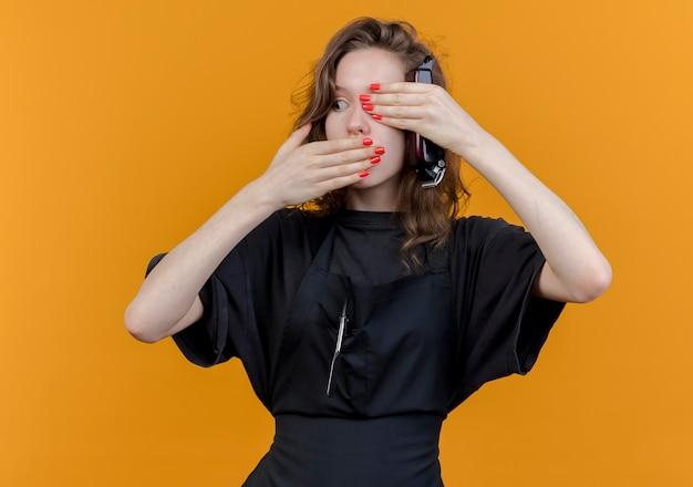 Młody słowiański fryzjer żeński noszenie munduru patrząc na bok trzymając maszynkę do strzyżenia włosów na białym tle na pomarańczowym tle