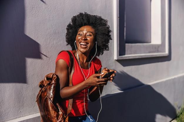 Młody śmiejąc się afrykańskiej kobiety stojącej na zewnątrz, trzymając inteligentny telefon i słuchając muzyki