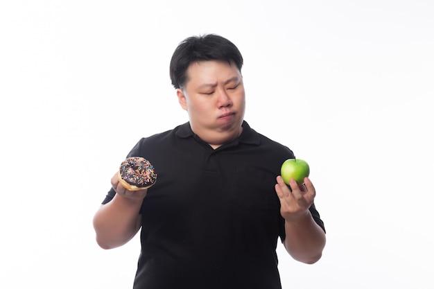 Młody śmieszny gruby azjatycki mężczyzna wybiera między czekoladowymi pączkami i zielonym jabłkiem